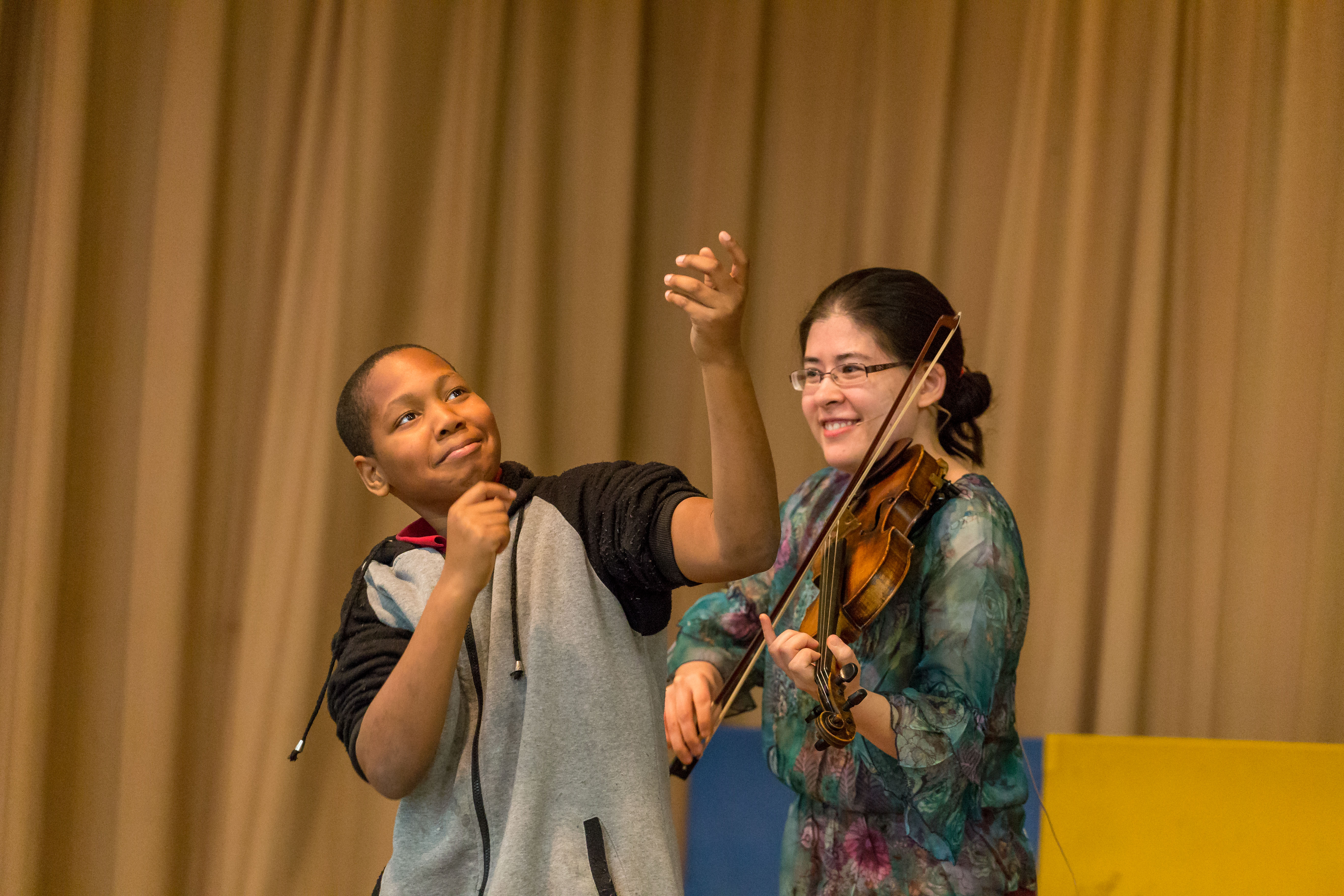 A child with his hands in the air with a woman playing the violin