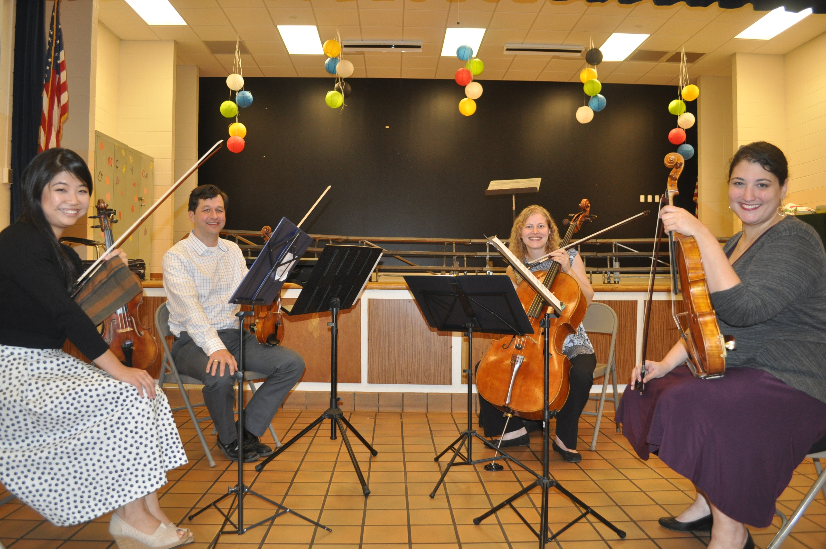 Four musicians playing stringed instruments