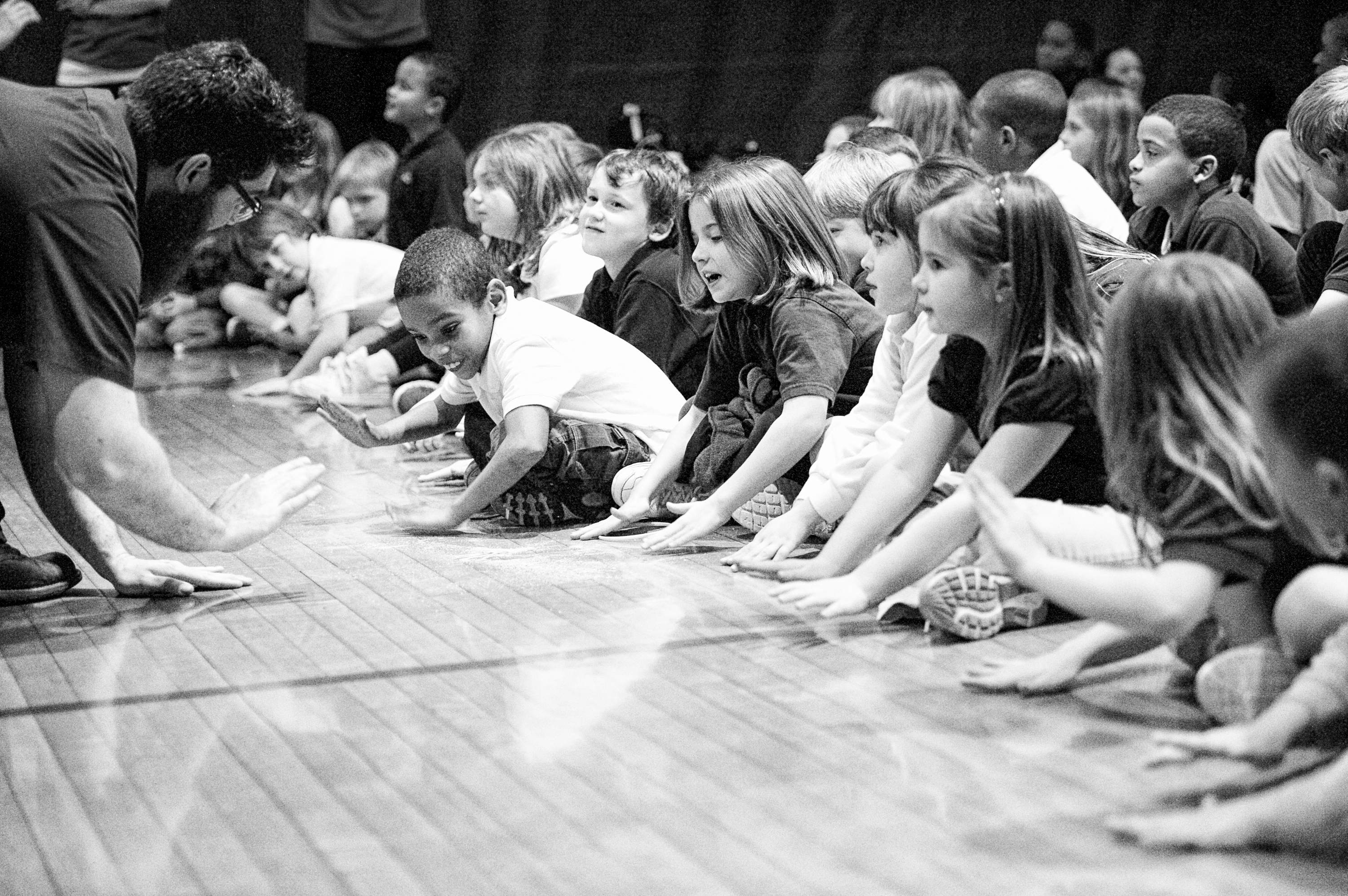 Children using their hands on a gym floor to make percussion sounds